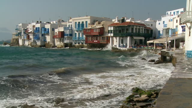 ws view of sea shore with tourists in restaurant and houses at little venice/ mykonos, cyclades, greece - mykonos stock videos and b-roll footage