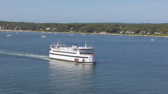 WS AERIAL POV View of sea with steam liner and Martha's Vineyard island, tree area in background / Falmouth, Massachusetts, United States