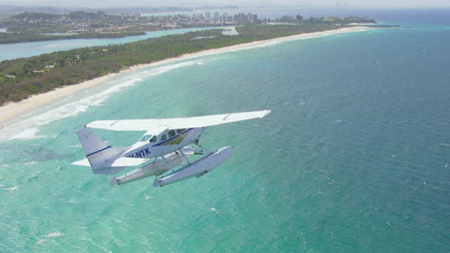 MS AERIAL View of seaplane flying over beach / Kings Cliff, New South Wales, Australia