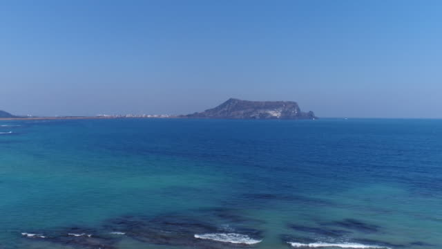 View of seascape and Seongsanilchulbong Tuff Cone (Korea Natural Monument 420) in distance