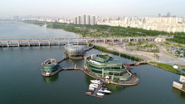 vídeos y material grabado en eventos de stock de view of sebitdungdungseom island (artificail island floating on the han river) and banpodaegyo bridge in seoul at day - anclado