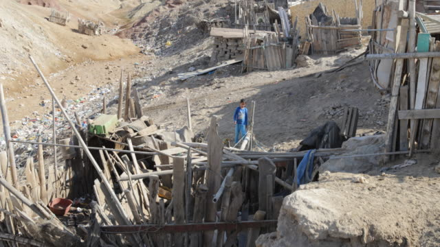 View of self made huts in the middle of a rocky and dry landscape in a slum in Tortuga Peru a girl is walking towards a hut