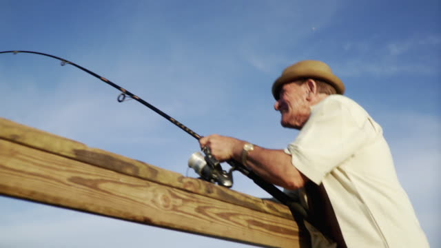 ms view of senior man fishing on pier / jacksonville beach, florida, usa     - one senior man only stock videos and b-roll footage
