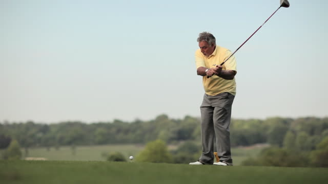 vídeos y material grabado en eventos de stock de ws view of senior man taking shot at golf course / canterbury, kent, uk - golf