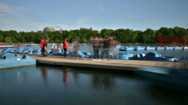 ws t/l view of serpentine hyde park and boat jetty with pedal boats moving in and out and tourists enjoying summer day in water / london, greater london, united kingdom - pedal boat stock videos and b-roll footage