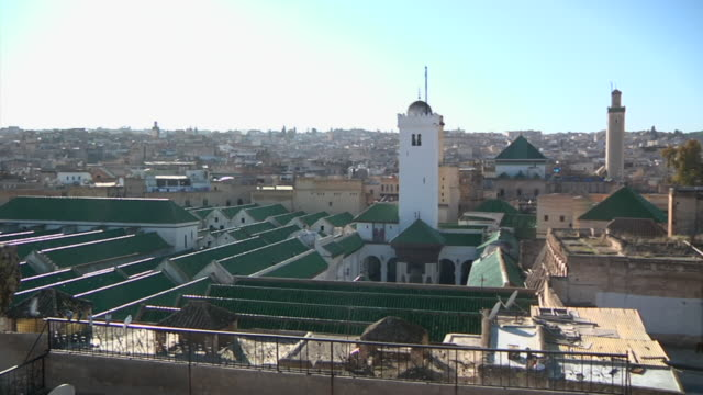 ws view of several buildings with green tops in city / fes, centro-north, morocco - minareto video stock e b–roll