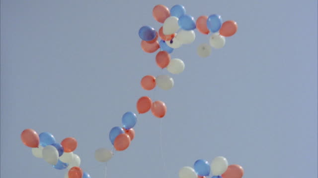 ms zi view of several color balloons drifting up into sky - balloons stock videos and b-roll footage