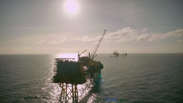 WS AERIAL DS SLO MO View of several oil rigs in / The North Sea