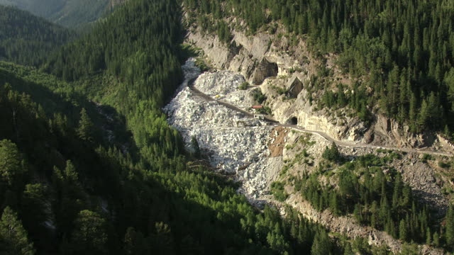 ms aerial view of shady mountainside with trees and mine entrance with equipment / marble, colorado, united states - rock face stock videos and b-roll footage
