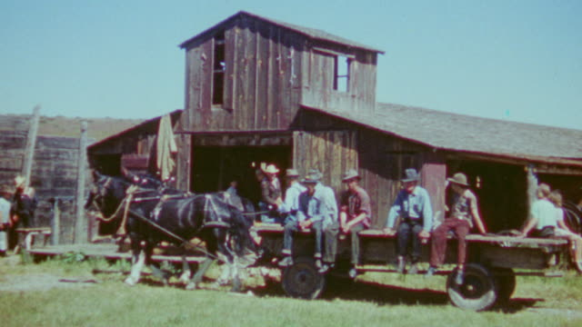 WS View of sheep ranch workers at barn on flatbed wagon and horse car passing by