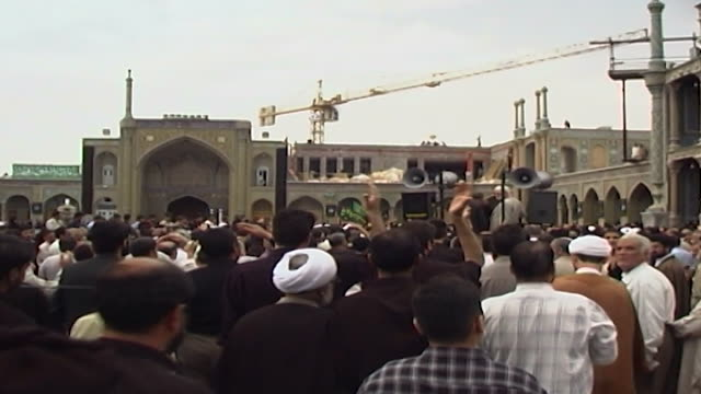 view of shia clerics and iranians in a funerary procession, beating their heads outside the fatima masumeh shrine. - shi'ite islam stock videos & royalty-free footage