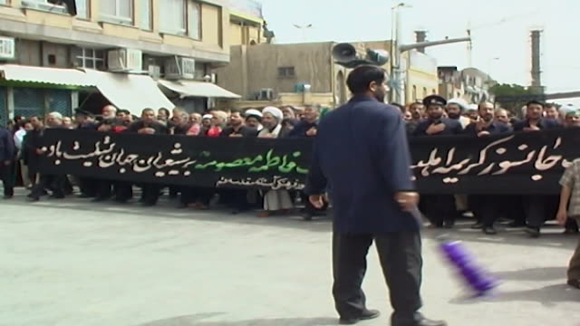 view of shia clerics and men beating their chests and holding a banner condoling fatima daughter of the prophet muhammad, marching in a procession... - shi'ite islam stock videos & royalty-free footage