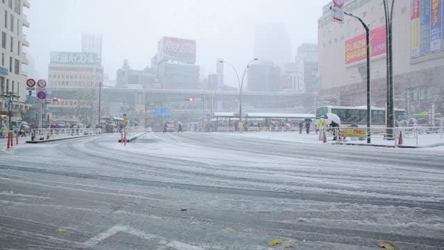 ws view of shibuya station west at snowy day / shibuya, tokyo, japan - 雪点の映像素材/bロール