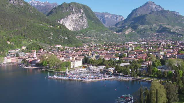 WS AERIAL View of ships at harbor and village near lake / Lake Garda, Trentino, Verona, Brescia