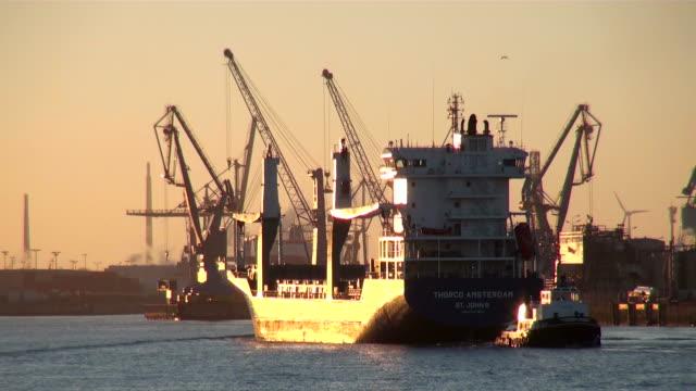 ws view of shipyard and ship floating in river with small boat / hamburg, hamburg, germany - shipyard stock videos & royalty-free footage