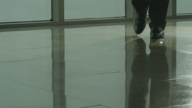 View of shoes of businessman walking throgh a corridor