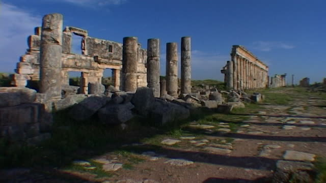 view of shop fronts and houses behind the columns of the great colonnade, which is one of the longest in the roman world. apamea was looted and... - 長さ点の映像素材/bロール