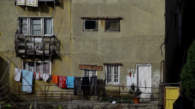 vidéos et rushes de ms view of side facade of an apartment building in valparaiso with clothing on line  / valparaiso, chile  - wiese