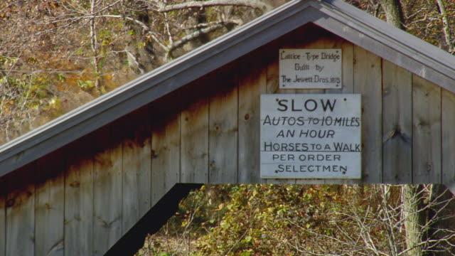 vídeos y material grabado en eventos de stock de ws arieal view of sign board on seven covered bridge / vermont, united states - escritura occidental