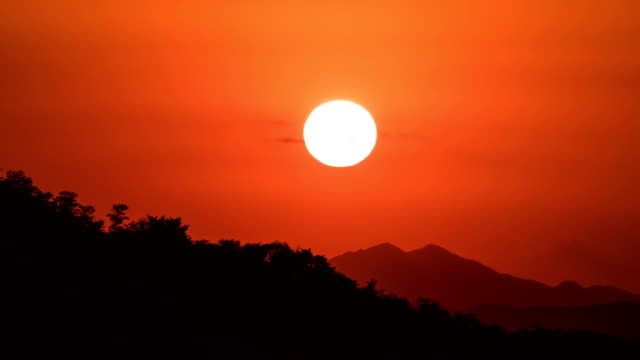 View of Silhouette mountain and Setting sun with orange sky