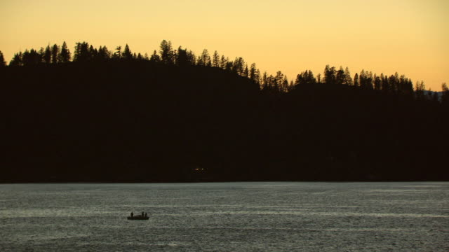 ws aerial view of silhouette people in boat in flathead lake at dusk with orange sky / montana, united states - flathead lake stock videos and b-roll footage