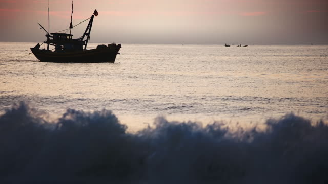 vidéos et rushes de ws view of silhouetted fishing boat and fisherman at work motor across silver sea / mui ne, vietnam - pêcheur