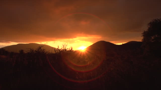 ws view of silhouetted hills at sunset / pilanesberg national park, north west province, south africa - sundog stock videos & royalty-free footage