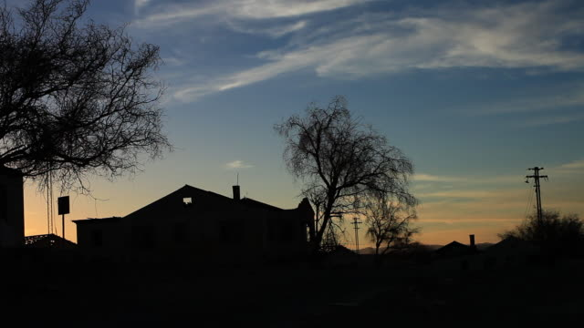 ms view of silhouetted house and trees in sunset light / san pedro de valdivia, atacama desert, chile - travelling light stock videos & royalty-free footage