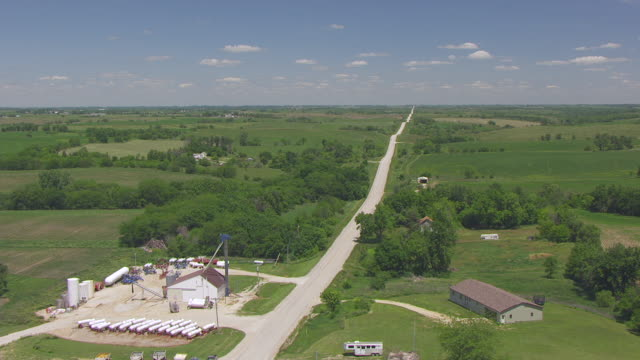 ws aerial pov view of silos near road in farmland / madison county, iowa, united states - iowa stock videos & royalty-free footage