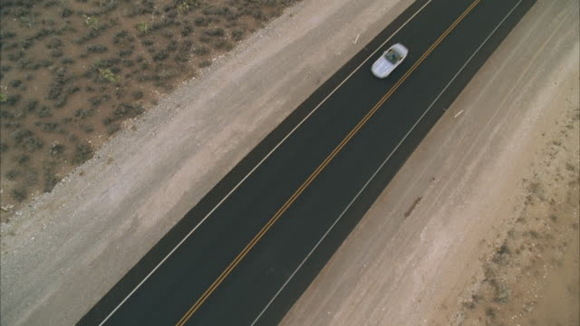 ws aerial view of silver convertible sports car on desert road  - convertible overhead stock videos & royalty-free footage