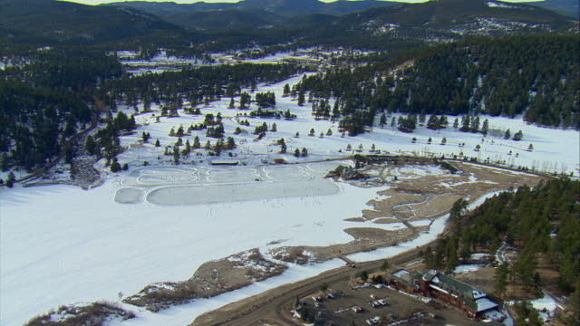 WS ZI PAN View of skaters on frozen Evergreen Lake in Rocky Mountains / Denver, Colorado, USA
