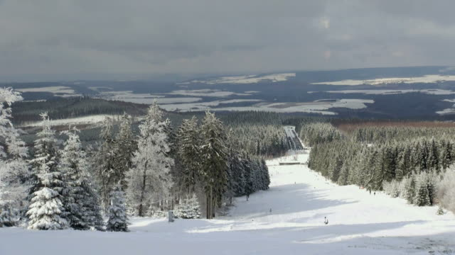 ws view of skier and snowboarder on piste, winter sport and snow ski lift / erbeskopf, hunsruck, rhineland palatinate, germany - vacanza sulla neve video stock e b–roll