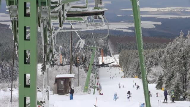 ws view of skier and snowboarder on piste, winter sport, and snow ski lift / erbeskopf, hunsruck, rhineland palatinate, germany - bastoncino da sci video stock e b–roll