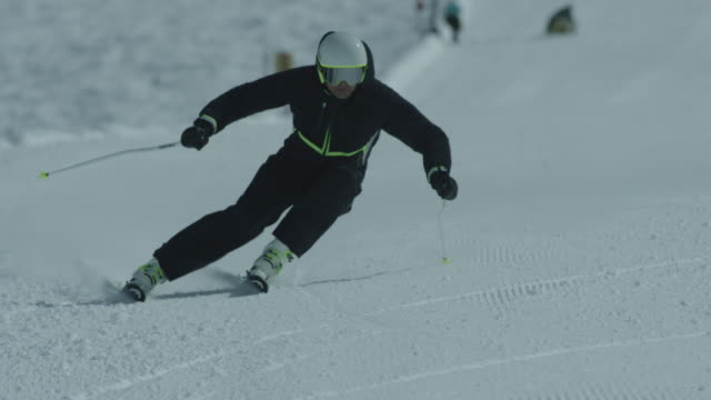 View of skier skiing down snowy slope.