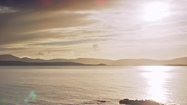 ws pan view of skye island mountains near dunvegan head with sun and clouds / skye island, scotland, united kingdom - 2k resolution stock videos and b-roll footage