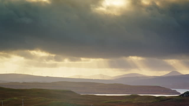 vidéos et rushes de ws t/l pan view of skye island wind turbines with sun rays and clouds / skye island, scotland, united kingdom - îles hébrides