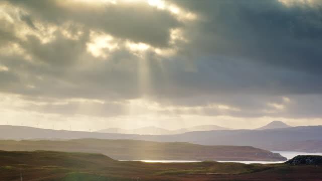 vidéos et rushes de ws view of skye island wind turbines with sun rays and clouds / skye island, scotland, united kingdom - îles hébrides