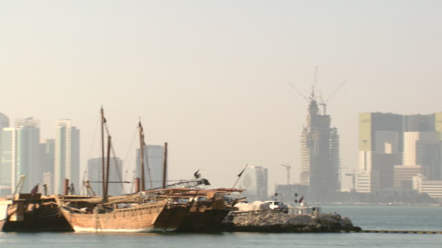 ws pan view of skyline of city and moored boats / doha, qatar - doha stock videos & royalty-free footage
