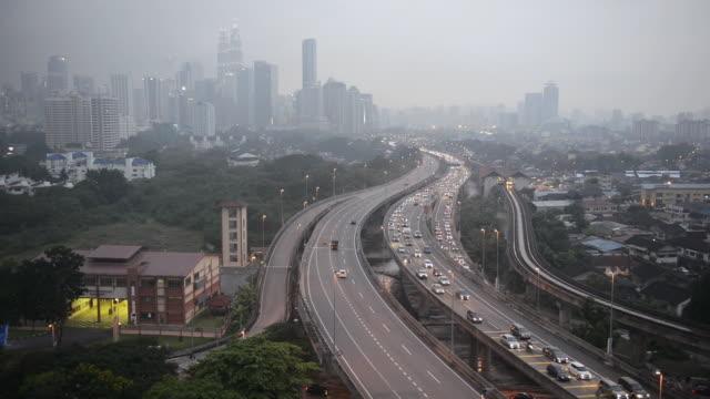 ws view of skyline with traffic moving on bridge / kuala lumpur, malaysia - マレーシア点の映像素材/bロール