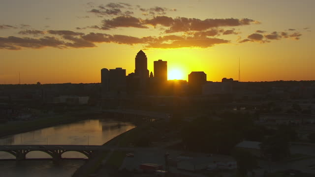 WS AERIAL POV View of skyscrapers at sunset in city / Des Moines, Iowa, United States