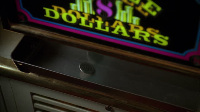 vidéos et rushes de cu view of sliver dollar coins dropping into slot machine tray in las vegas casino / las vegas, nevada, usa - chance