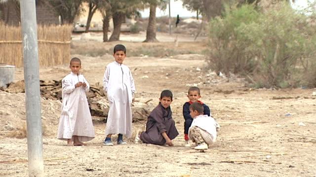view of small boys playing in the marsh arab village of al-chubayish in shiite dominated southern iraq. - 足根点の映像素材/bロール