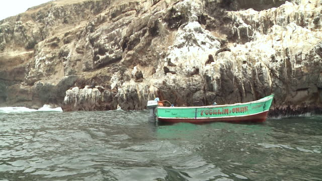 WS View of Small fishing boat very close to rocky cliffs in ebbing waves, fisherman aboard fishes, sea lions on rocks / Lima, Peru