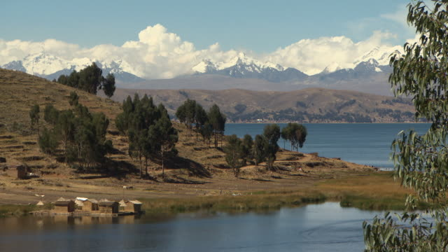view of small huts on lake titicaca, with trees on hill, further view of lake and snow capped mountains in b/g, near tiwanaku tiahuanaco/tiahuanacu, bolivia - ボリビア点の映像素材/bロール