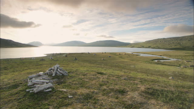 vidéos et rushes de ws view of small tents near lake bank with mountains in background / lappland, sweden - camping