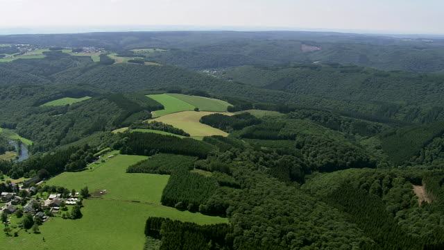 ws aerial view of small town set of in trees covered mountain at countryside / luxembourg - luxembourg benelux stock videos & royalty-free footage