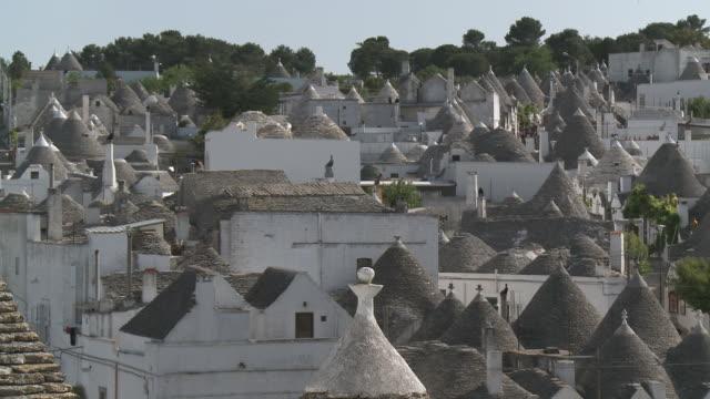 vídeos de stock, filmes e b-roll de ms view of small town with trulli of alberobello  at unesco world heritage / alberobello, puglia, italie - pequeno