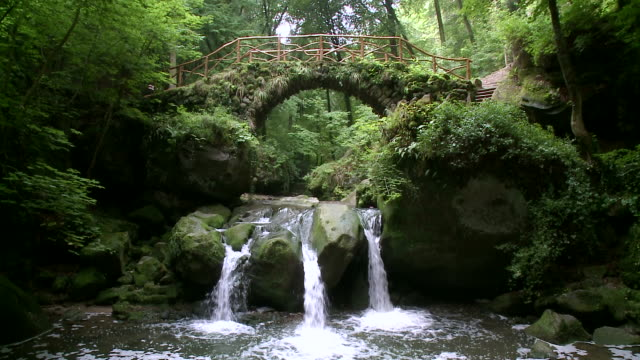 ms view of small waterfall below wooden bridge in forest / mã¼llerthal, luxembourg - small stock videos & royalty-free footage