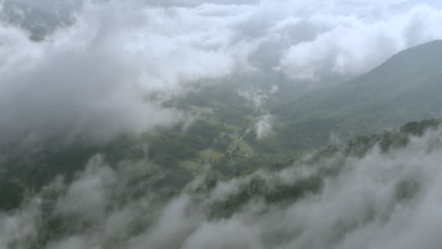 WS AERIAL POV View of Smoky Mountains with valley trough fog, river bends seen in distance / Mitchell County, North Carolina, United States