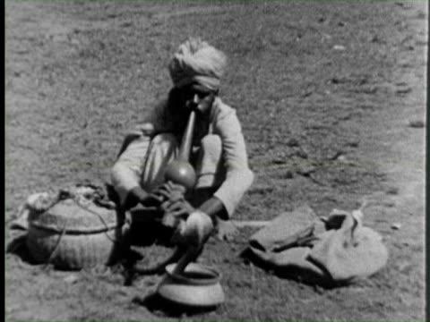b/w view of snake charmer with snake  audio / india - 中年の男性一人点の映像素材/bロール